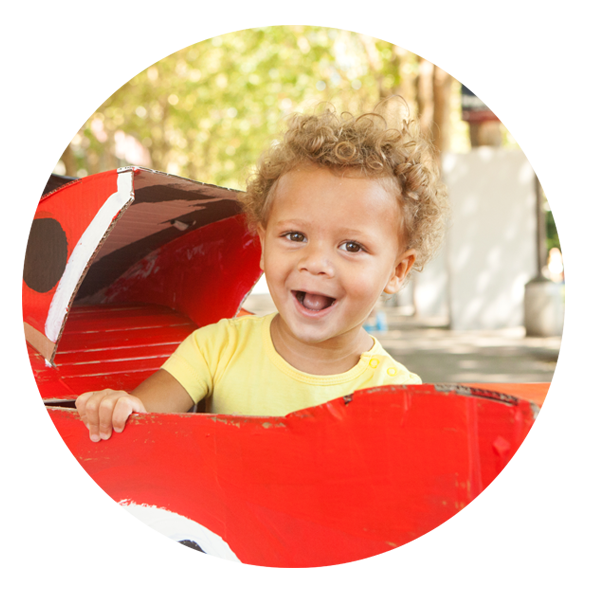 Happy infant sitting in red toy